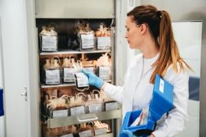 Woman grabbing plasma out of a plasma storage freezer.